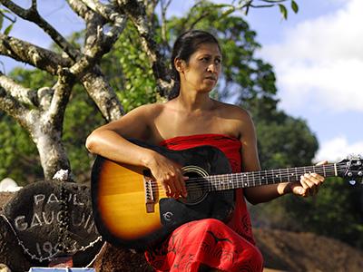 Marquisienne sur la tombe de Paul Gauguin - © GIE Tahiti Tourisme - P. Bacchet